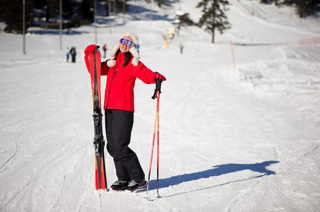 Conceito de férias e esporte de inverno com mulher com esquis nas mãos ao pé da montanha Foto Premium