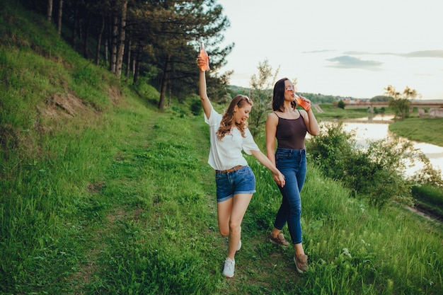 Conceito de férias e felicidade, duas garotas se divertem, bebem coquetel na garrafa, diversão de verão, ao pôr do sol, expressão facial positiva, ao ar livre Foto Premium