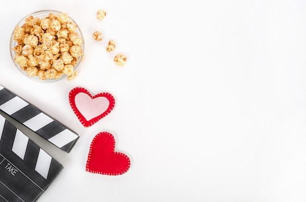 Conceito de filme do dia dos namorados. claquete com corações e pipoca de caramelo com espaço de cópia em um fundo branco. Foto Premium