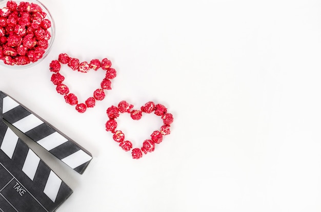 Conceito de filme do dia dos namorados. claquete com corações feitos de pipoca de caramelo vermelho com espaço de cópia em um fundo branco. Foto Premium