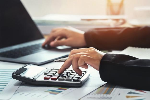 Conceito de finanças contábeis de negócios. contador usando calculadora para calcular com laptop trabalhando no escritório Foto Premium