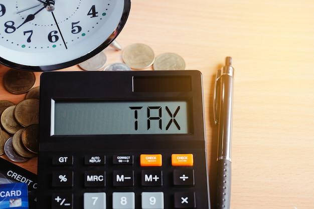Conceito de finanças de negócios fiscais 2021. calculadora com dinheiro e cartão de crédito na mesa. pagamento anual de impostos Foto Premium