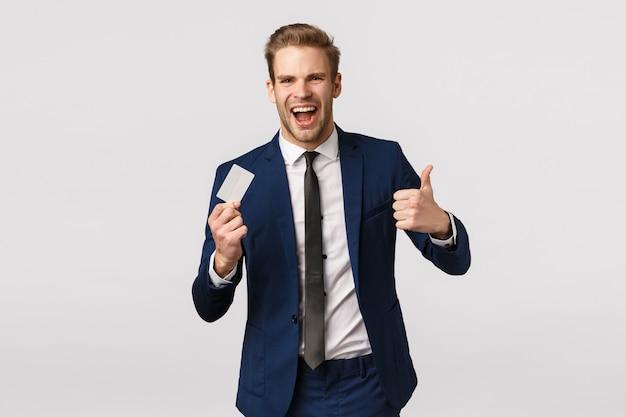 Conceito de finanças, negócios e riqueza. alegre e bonito jovem empresário loiro mostrando o polegar para cima em aprovação, como gesto de segurar o cartão de crédito, recomendar serviços bancários, fazer compra Foto Premium