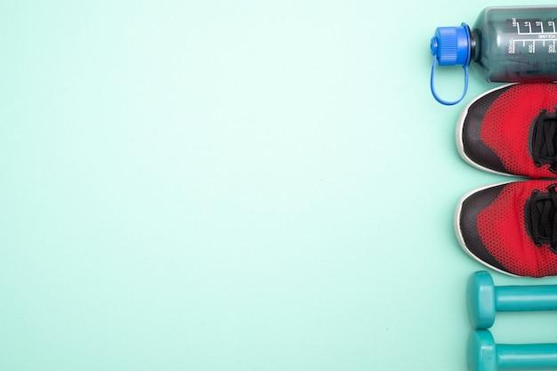Conceito de fitness com tênis, halteres e garrafa de água Foto Premium