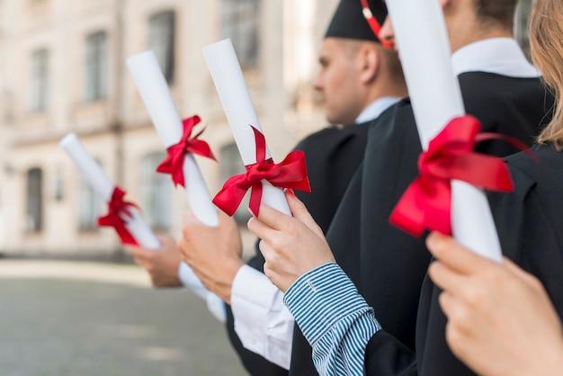 Conceito de formatura com estudantes segurando seus diplomas Foto gratuita