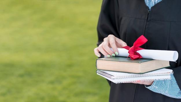 Conceito de formatura com o aluno segurando o livro e diploma Foto gratuita