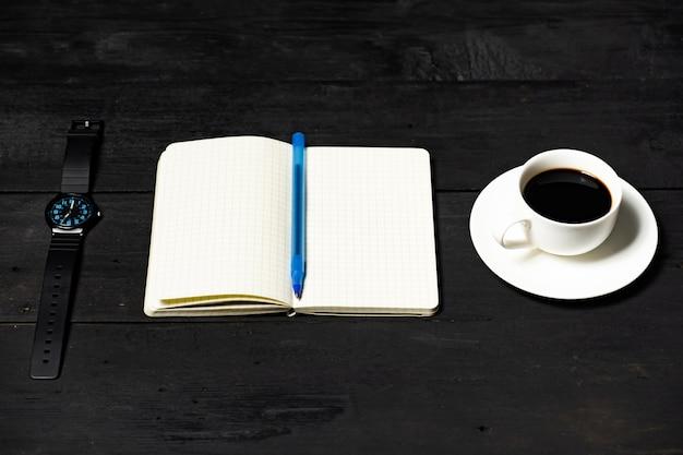 Conceito de gerenciamento de tempo. bloco de notas, xícara de café e relógio mecânico na superfície de madeira preta Foto Premium