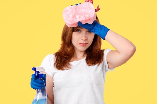 Conceito de higiene e limpeza. cansado onworked feminino em luvas de borracha e camiseta branca, sente fadiga depois de fazer tarefas domésticas, esfrega a testa, detém limpador e esponja, isolado na parede amarela Foto gratuita