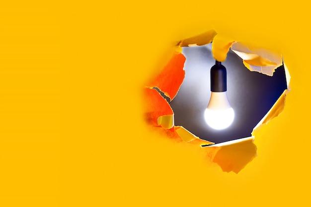 Conceito de ideia criativa. uma lâmpada brilha no buraco do papel amarelo Foto Premium