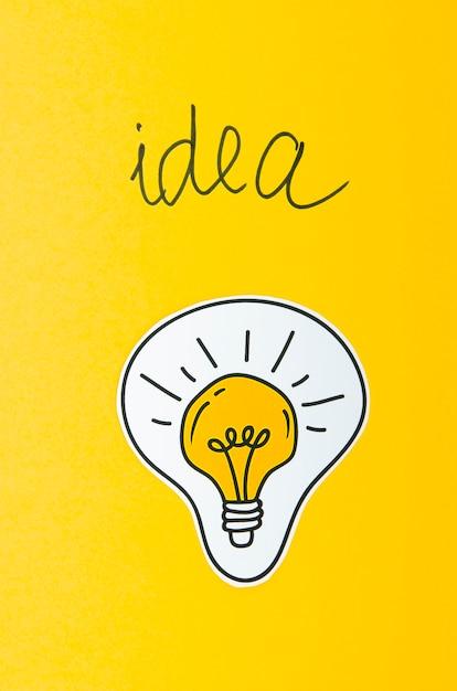 Conceito de idéia de lâmpada em fundo amarelo Foto gratuita