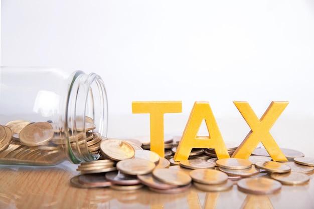 Conceito de imposto. o imposto da palavra pôs sobre moedas e garrafas de vidro com moedas para dentro no fundo branco. Foto Premium