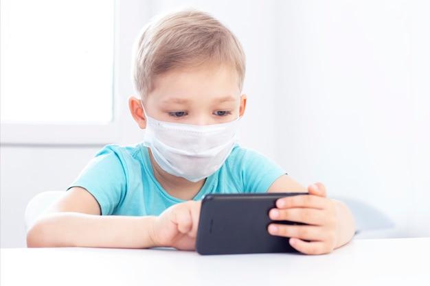 Conceito de infecção por coronavírus. menino em uma máscara médica se senta em uma cadeira dentro de casa e toca um gadget. Foto Premium