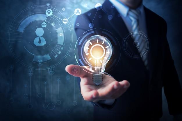 Conceito de inovação e tecnologia, empresário segurando segurando lâmpada de iluminação criativa com linha de conexão para se comunicar Foto Premium