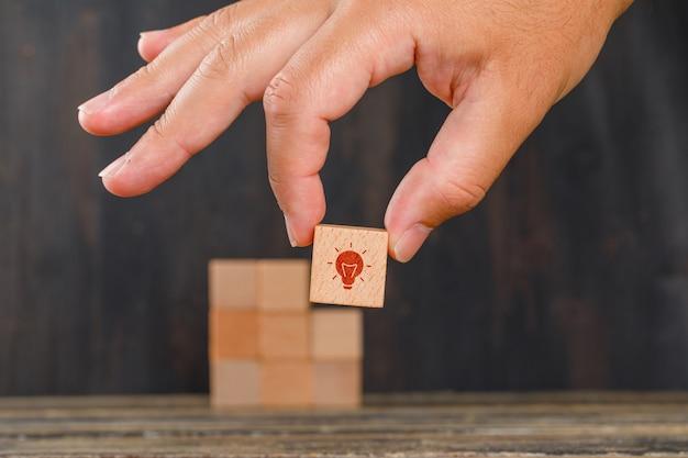 Conceito de inovação na vista lateral da mesa de madeira. mão segurando o cubo de madeira com ícone. Foto gratuita