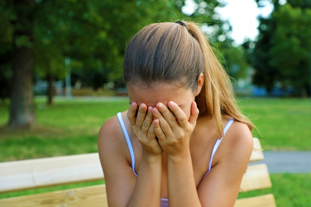 Conceito de intimidação, discriminação ou estresse. adolescente triste chorando sozinho no parque. jovem estudante chateada com ansiedade. Foto Premium
