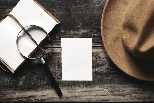 Conceito de jogo de detetive misterioso. caderno aberto em capa de couro, folha de papel branco, chapéu marrom de feltro e óculos grandes de aço com lupa vintage isolados na mesa de madeira preta envelhecida. vista do topo. Foto gratuita