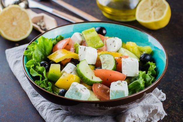 Conceito de lanche de comida saudável. salada grega tradicional com legumes frescos, queijo feta e azeitonas pretas Foto Premium