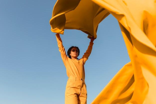 Conceito de liberdade com mulher segurando o pano na natureza Foto gratuita