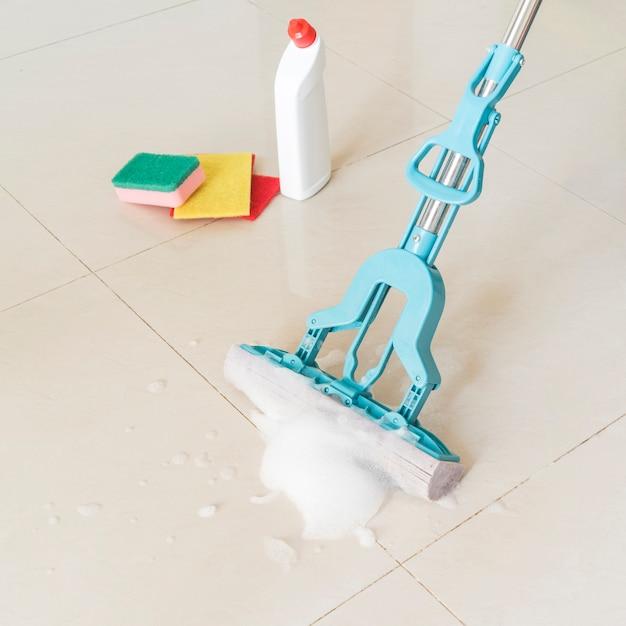 Conceito de limpeza com garrafa de plástico e esfregão Foto gratuita