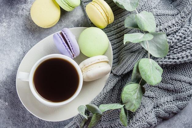 Conceito de manhã aconchegante. macarons pastel coloridos deliciosos com creme e café, camisola cinzenta morna Foto Premium