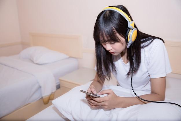 Conceito de manhã, lazer, natal e as pessoas - jovem feliz na cama no quarto de casa Foto gratuita