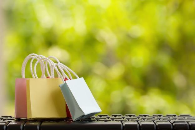 Conceito de marketing / pagamento on-line: sacolas com smartphones no teclado do computador, compras on-line de ícone e redes de mídia social. retrata o consumidor compra bens, produtos e serviços da internet Foto Premium