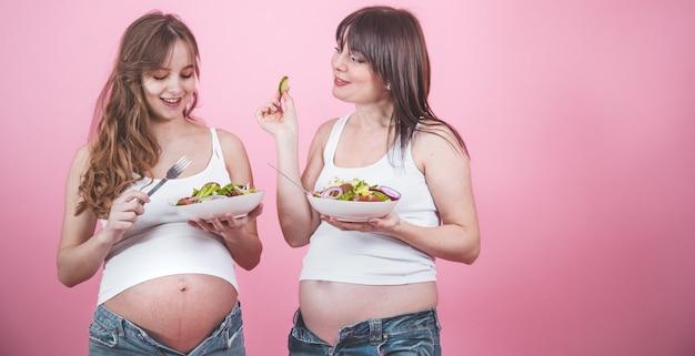 Conceito de maternidade, duas mulher grávida comendo salada fresca Foto gratuita
