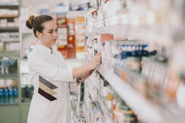 Conceito de medicina, farmacêutica, saúde e pessoas. farmacêutico feminino tomando medicamentos da prateleira. Foto gratuita
