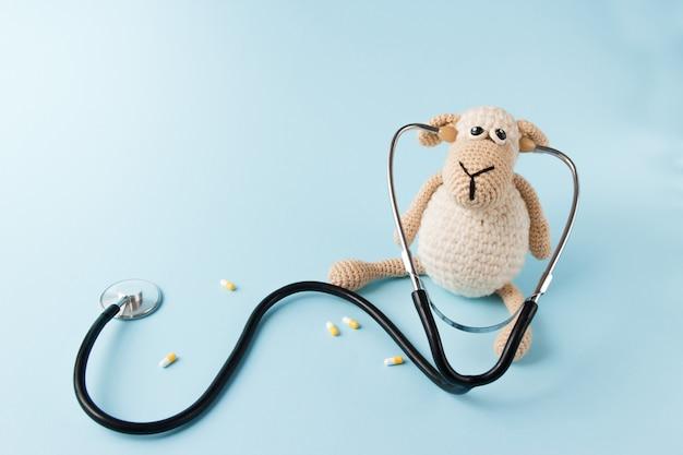 Conceito de médico infantil. brinquedo de ovelhas e estetoscópio em fundo azul Foto Premium