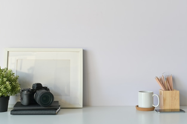 Conceito de mesa de fotógrafo. mesa de designers, câmera, café e foto frame espaço de cópia. Foto Premium