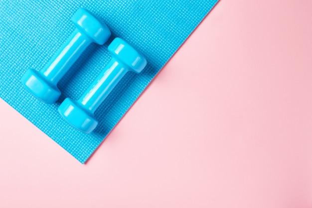 Conceito de minimalismo de fitnes. halteres e sutiã esportivo em um fundo azul e rosa Foto Premium