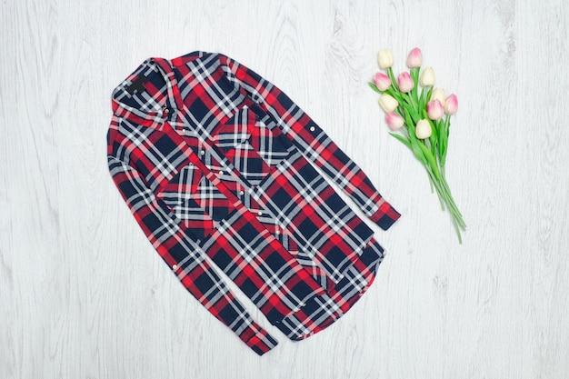 Conceito de moda. camisa quadriculada vermelha e tulipas cor de rosa. fundo madeira Foto Premium