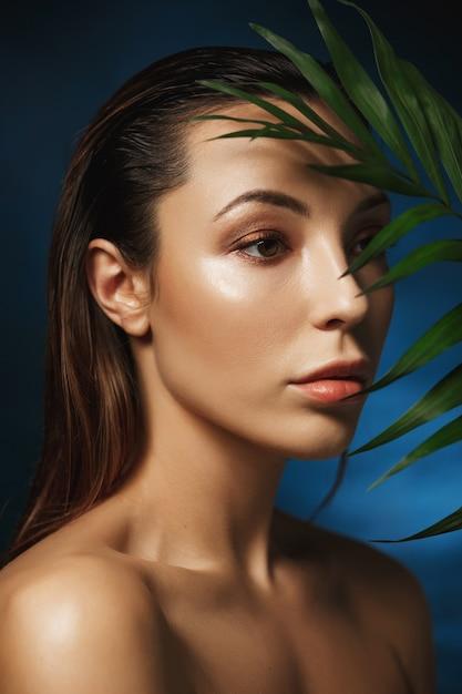 Conceito de moda. closeup de mulher incrível na parede azul escuro com folhas Foto gratuita