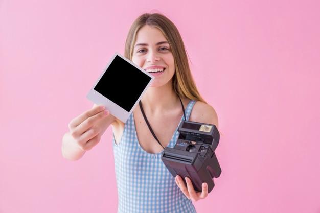 Conceito de moda de verão com mulher mostrando polaroid Foto gratuita