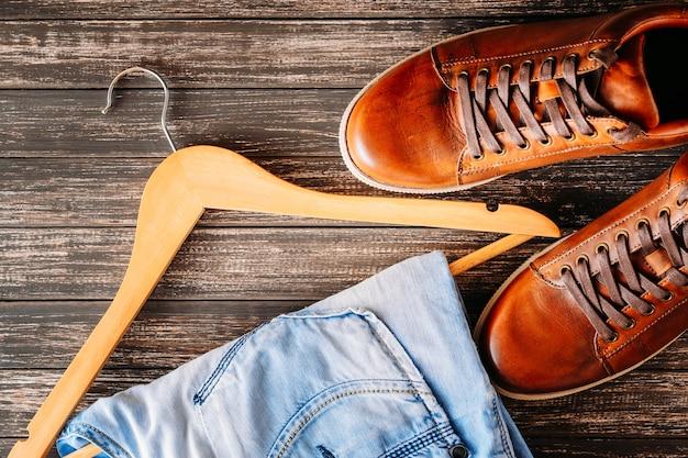 Conceito de moda do homem. sapatos masculinos de couro casual marrom, jeans e cabide em um fundo escuro Foto Premium