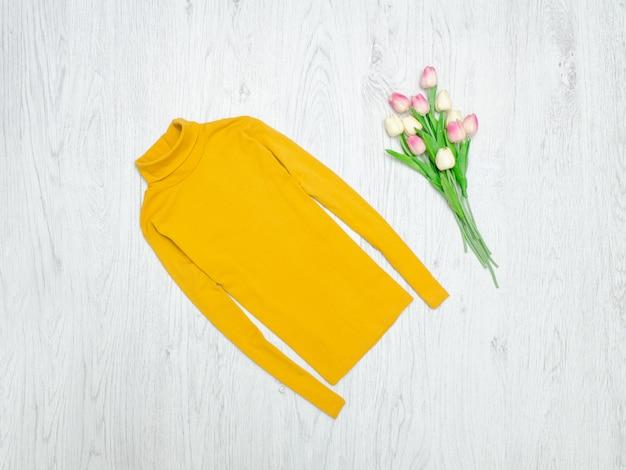 Conceito de moda. gola alta amarela e tulipas cor de rosa. fundo madeira Foto Premium