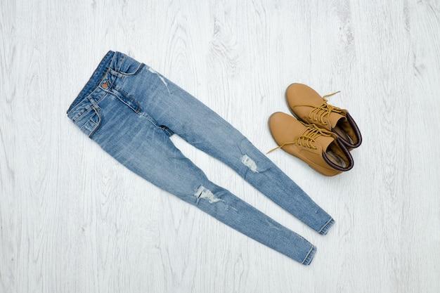 Conceito de moda. jeans e botas rasgados azuis. fundo madeira Foto Premium