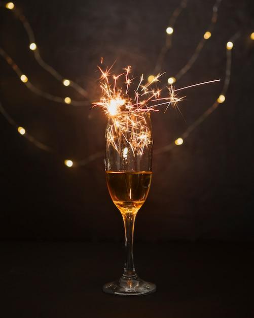 Conceito de natal com taça de champanhe e fogos de artifício Foto gratuita