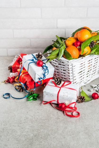 Conceito de natal e ano novo tangerinas frescas com folhas verdes em uma cesta branca decoração de natal e caixas de presente na mesa cinza Foto Premium