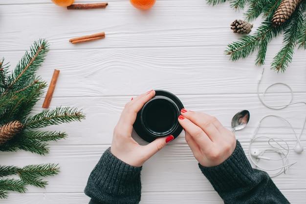 Conceito de natal, wooman segurando a xícara de café Foto Premium