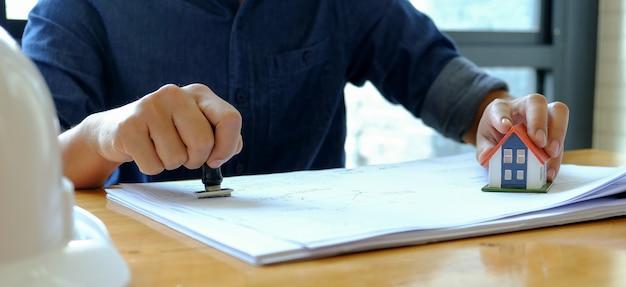 Conceito de negociação imobiliária, pessoal segurando um carimbo de borracha na mão para aprovar as vendas. Foto Premium