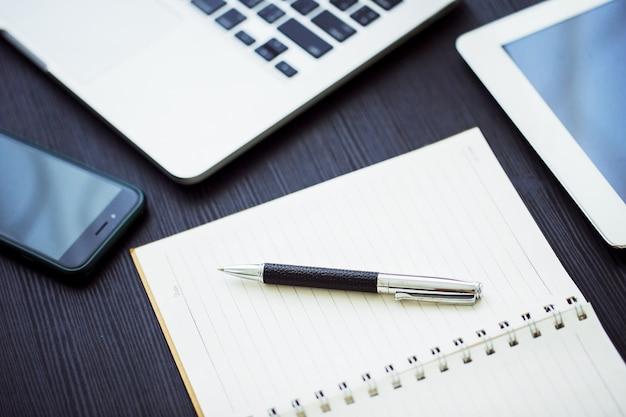 Conceito de negócio, no local de trabalho do escritório com o laptop na mesa de madeira contra as janelas Foto Premium