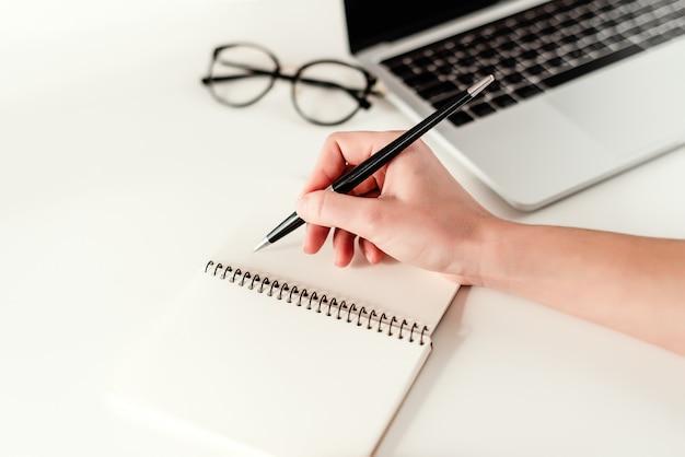 Conceito de negócio - trabalho em um escritório moderno brilhante com um laptop, notebook e óculos Foto Premium