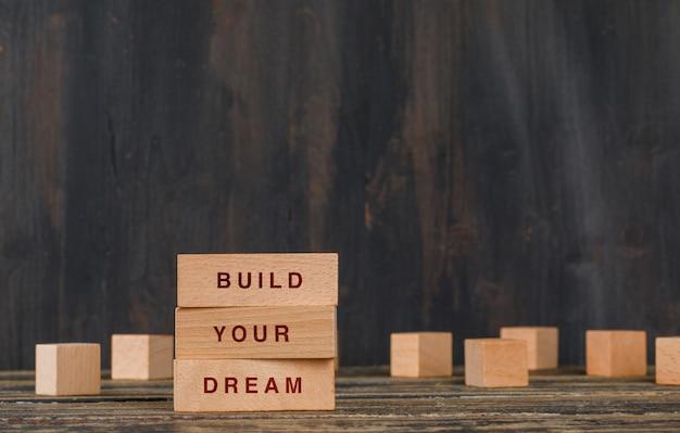 Conceito de negócios e motivação com blocos de madeira na vista lateral para a mesa de madeira. Foto gratuita