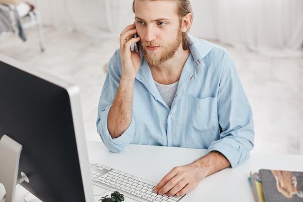 Conceito de negócios, escritório e tecnologia. vista superior do empregado barbudo vestindo camisa azul, falando no telefone com companheiros, digitando no teclado, olhando na tela do computador, usando dispositivos modernos Foto gratuita