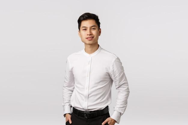 Conceito de negócios, sucesso e bem-estar. bonito jovem empresário asiático trabalhando com finanças, ter sorte, segurar as mãos nos bolsos, sorrindo seguro de si Foto Premium