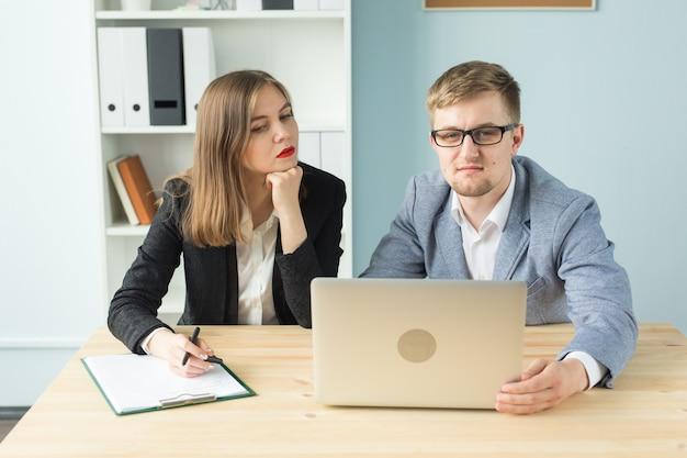 Conceito de negócios, trabalho em equipe e pessoas - dois colegas discutindo algum projeto interessante no escritório. Foto Premium