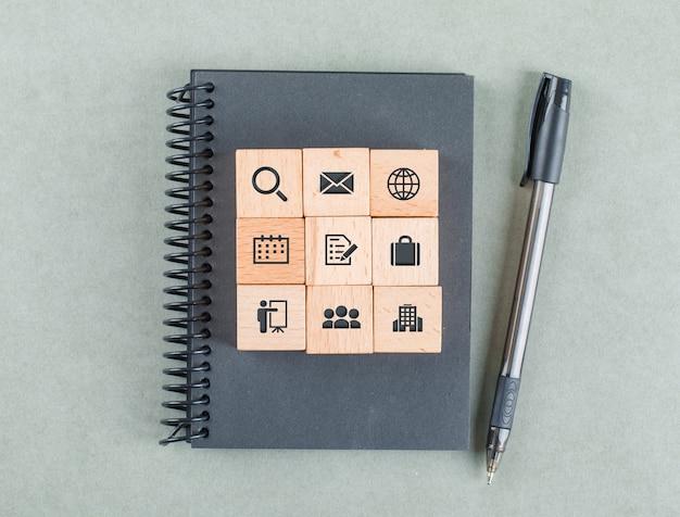 Conceito de notas de negócios com blocos de madeira com ícones, caderno, lápis na vista superior de mesa de cor sábia. Foto gratuita