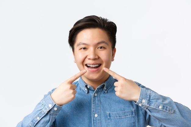 Conceito de ortodontia e estomatologia. close-up de um homem asiático sorridente e feliz apontando o dedo para o aparelho dentário nos dentes com uma expressão satisfeita, recomendar clínica dentista, parede branca de pé Foto gratuita