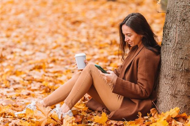 Conceito de outono - mulher bonita tomando café no parque outono sob folhagem de outono Foto Premium